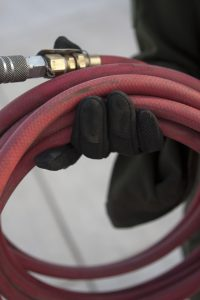 Person holding red air hose with brass fitting