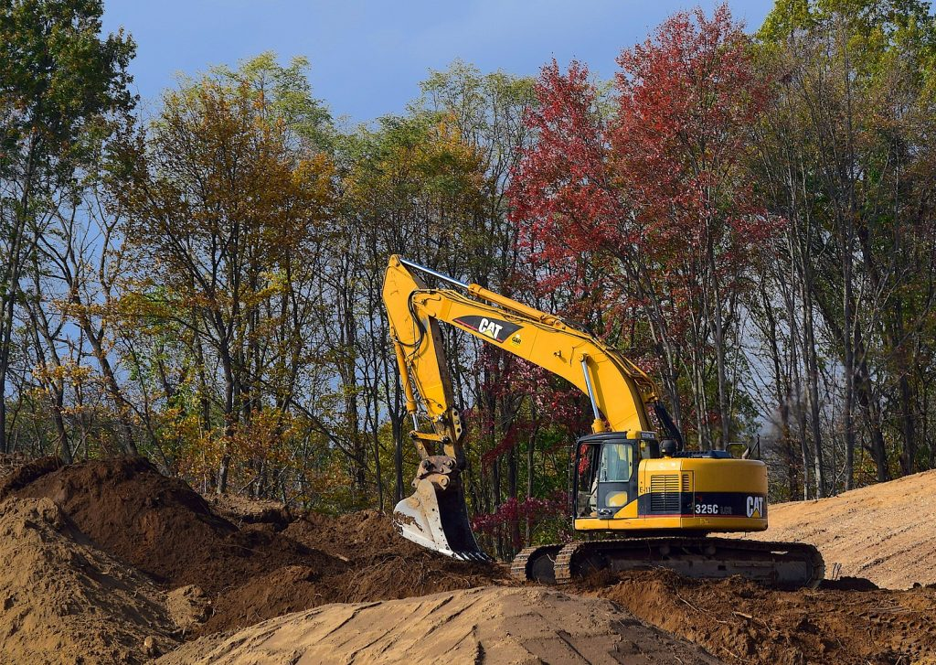 Excavator digging in woods