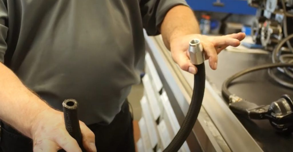 person holding hydraulic hose assembly